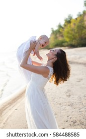 A young mother holding a baby in her arms on the beach by the sea