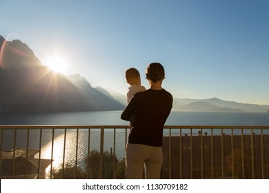 Young mother holding baby looking at mountains sunrise, sea landscape, dreaming of happy future for her child, single mom with little kid relaxing on travel vacation. Italy, Lombardia, Riva di Solto