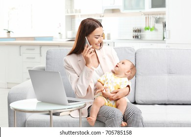 Young mother holding baby while talking on phone in home office