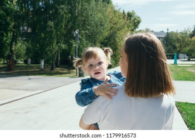Young mother holding daughter in her arms during a walk in a city park on a warm sunny day