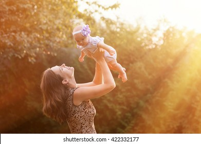 young mother holding daughter in her arms