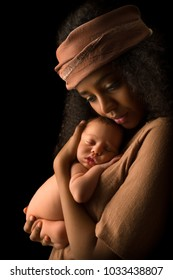 young mother holding her 7 days old little baby against a dark background