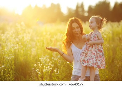 Young mother holding her adorable toddler girl at sunset