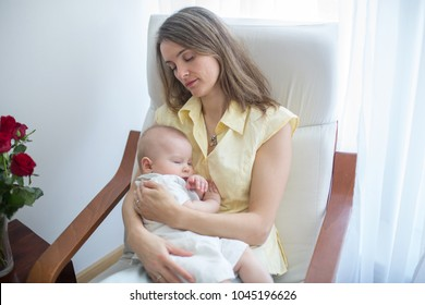Young mother holding her baby, rocking him to sleep, sitting in armchair in a cozy sunny bedroom