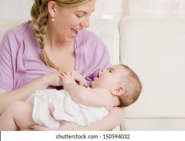 Young mother holding her baby girl in her arms and playing with her while sitting on a white sofa at home, enjoying motherhood and having fun.