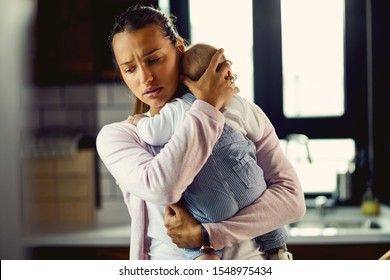 Young mother holding her baby son and consoling him at home.