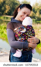 A young mother holding her baby in carrier