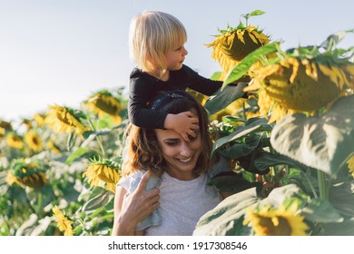 Young mother holding her baby. Mother and  little daughter having good time in the Sunflower field. Mothers Day. Family Concept