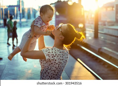 Young mother holding her baby on a train station