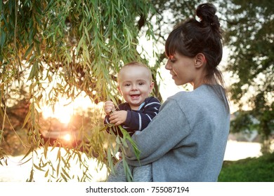 Young mother holding her baby boy in the park with the lake. Mother and new born boy having good time in the evening. Baby boy is holding the branch of willow treeand looking at the camera.