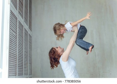 Young mother holding her child. Woman and little girl relax in a white bedroom near the window. Happy family at home. Young mother playing with her daughter