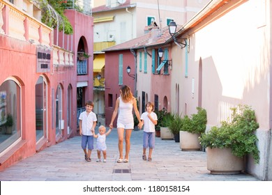 Young mother, holding her children hand in hand, walking on colorful street in the town of Villefrance, French Riviera