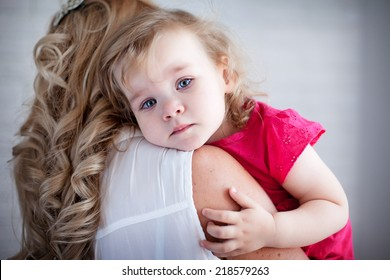 Young mother holding her crying baby girl