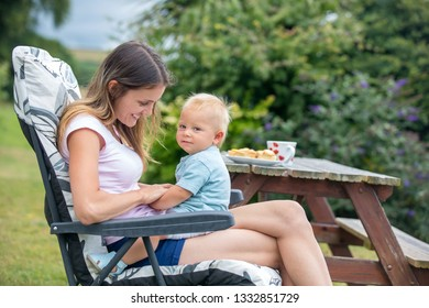 Young mother holding her cute baby boy, cuddle him, hugging and kissing, smiling happily, rural outdoor cozy place