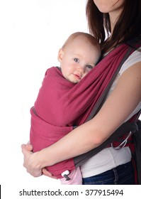 Young mother holding her cute daughter in baby carrier