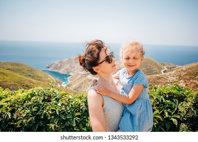 Young mother holding her daughter in her hands on mediterranean coast during vacation