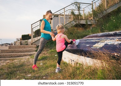 A young mother is holding her daughter's hand as they stretch their legs before they go for a run along the beach. The little girl is seen from behind. Mother and daughter are wearing fitness gear.