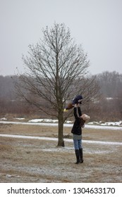 young mother is holding her little beautiful son above her head on ground covered with snow in winter with tree in the background