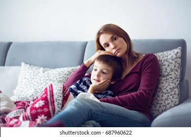 Young mother, holding her little sick boy, lying together on the couch