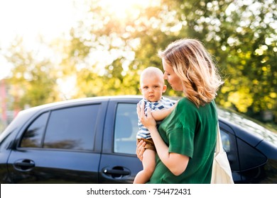 Young mother holding her little baby boy in the arms getting into the car.