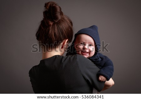 Young mother holding her little son with blue sweater with hood. Portrait of mother from back side and smiling son looking at camera from her shoulder in front of grey background.