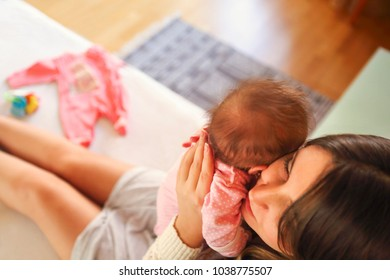 Young mother holding her newborn child. Mom nursing baby. Family at home. Close up