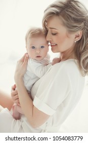 Young mother holding her newborn child. Mom nursing baby. Woman and new born boy relax. Nursery interior. Mother breast feeding baby. Family at home. Portrait of happy mother and baby
