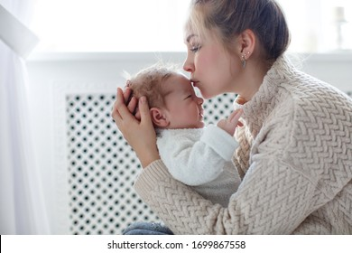 Young mother holding her newborn child. Mom nursing baby. Woman and new born boy relax. Nursery interior Family at home. Portrait of happy mother and baby