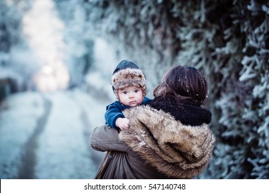 Young mother holding her newborn baby with cap with ear flaps. Mother and new born boy having good time in the park in winter. Baby boy is looking at the camera. Color toned image.