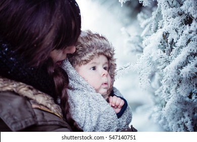 Young mother holding her newborn baby with cap with ear flaps. Mother and new born boy having good time in the park in winter. Baby boy is looking on the frozen branch. Color toned image.