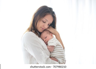 Young mother, holding her newborn baby boy at home in living room, back lit