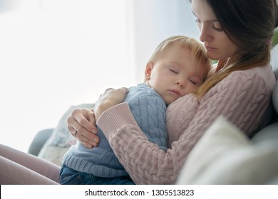 Young mother, holding her sick toddler boy, hugging him at home, sunny living room