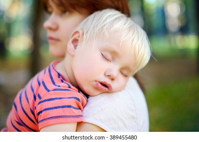 Young mother holding her sleeping toddler son