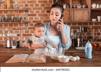 Young mother holding her son, talking on smartphone and preparing a dough in the kitchen. family life and multitasking concept