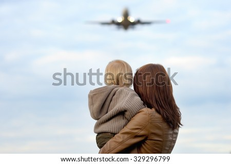 Young mother holding her toddler son with airplane on background