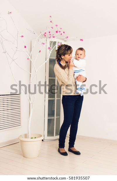 Young mother is holding little baby boy indoors