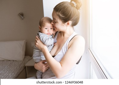 Young mother holding a newborn baby. Mom talks and laughs with her newborn son at home bedroom. Lifestyle happy multiracial family concept