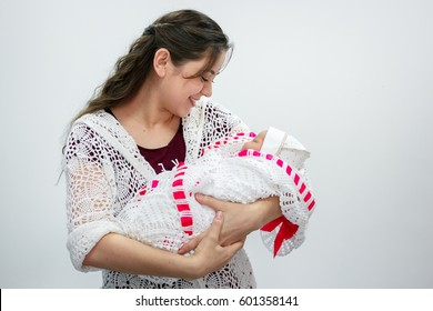 Young mother holding newborn daughter in her arms in the hall of the perinatal center