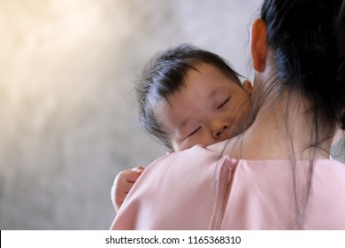young Mother holding sweet baby boy  and singing alullabiesfor her son to sleep, on concrete wall loft style background.