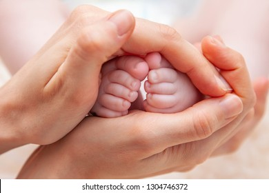 young mother holding sweet little legs