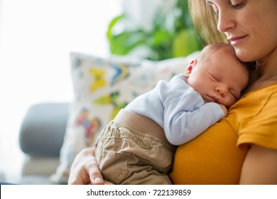 Young mother, holding tenderly her newborn baby boy, close portrait