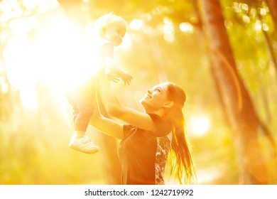 Young mother holds her son. Woman is having fun with her little baby in a summer park. Happy mom throws up child while playing outdoors