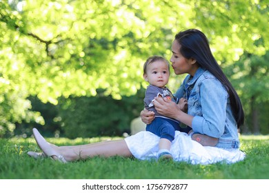 Young mother hugging her baby boy in her arms and giving a kiss while sitting under the tree at beautiful public park on summer sunny day.mixed race Asian-German family relaxing outdoor. Mother's Day