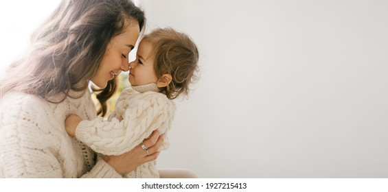 Young mother hugging her little daughter, they sitting near window and smiling.