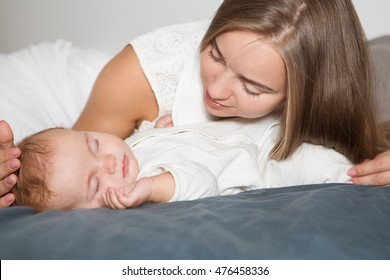 Young mother hugging her newborn child. Mom nursing baby. Woman and new born boy relax in a white bedroom. Family at home. Love, trust and tenderness concept.