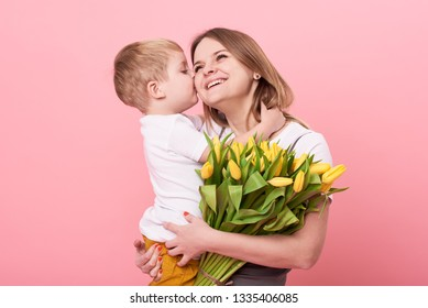 Young mother hugs his little son sitting on the floor against a pink background. Mom holds a bouquet of spring yellow flowers. Care and relationships and family concept. Mothers day