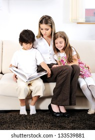 Young mother with kids reading on sofa