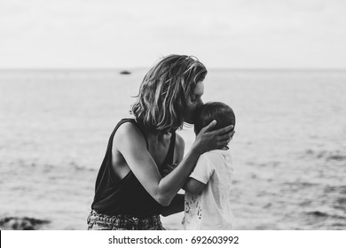 Young mother kisses baby near the sea. Black and white