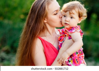 Young mother kissing baby daughter in park