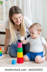 Young mother kissing her baby boy playing on on floor with colorful blocks